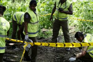 Police officers work at the explosion site in Pugoda on the east outskirts of Sri Lankan capital Colombo